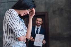 Selective focus of upset woman and angry collector with documents in room