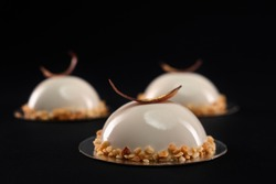 Selective focus of white half sphere cake decorated with nuts and chocolate feather. Desserts with smooth surfaces and mirror glaze isolated on black background. Tasty sweet dish in cafeteria.