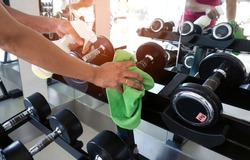 Selective focus of woman hand Prevention in Gym Cleaning Sport Equipment Dumbell with Antibacterial Disinfecting Wipe Against Virus. Disinfecting Fitness Equipment Concept.