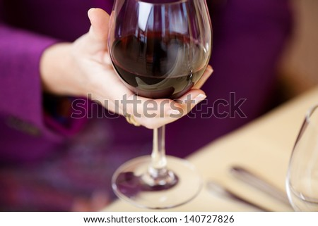Selective focus of woman's hand holding wine glass at restaurant table