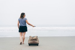 Selective focus of woman walks to the sea with a travel suitcase on a lonely beach and on a cloudy day, walks barefoot on the sand and looks to the right. Copy space