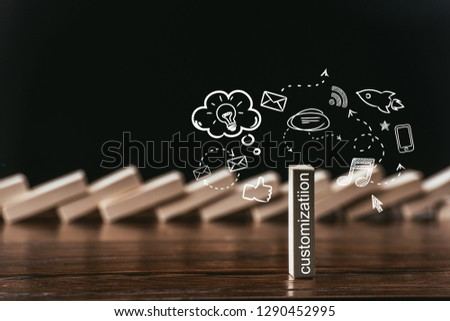 selective focus of wooden brick with word 'customization' and icons isolated on black ストックフォト ©