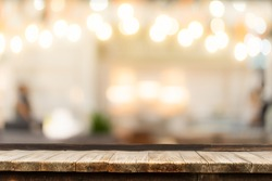Selective focus of wooden table in front of decorative indoor string lights. Christmas, festival and holiday concepts, can used for display or montage your product