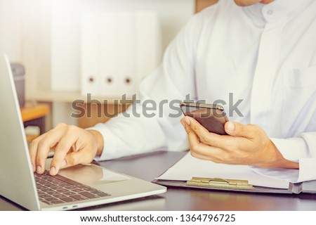Selective focus of Young business Arab Middle East muslim man using mobile smart phone with laptop in office