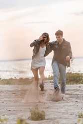 Selective focus of young couple throwing sand on sea cost at sunset
