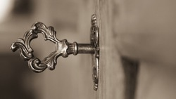Selective focus, old keyhole and key on a wooden antique door, vintage color tone process, business success concept