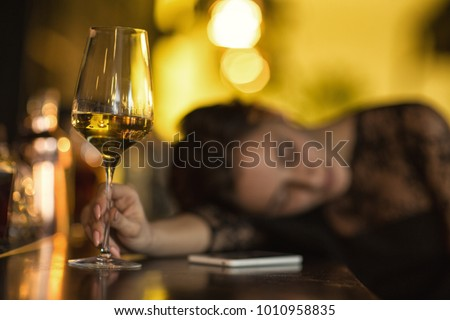 Selective focus on a glass of wine on the bar counter drunk woman sleeping after drinking too much on the background copyspace alcohol alcoholic passed out party depression depressed wasted addiction