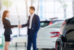 Selective focus on a new car and blur the dealership professional salesman and his client shaking hands. concept dealer Cars For Sale.
