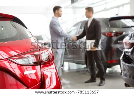 Selective focus on a new car at the dealership professional salesman and his client shaking hands on the background copyspace professionalism agreement contract leasing renting retail sales. #785113657