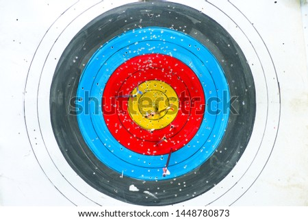 Selective focus on archery colorful target with blurred group of arrows in foreground. Sport and recreation leisure activity. Sport and recreation leisure activity.