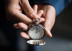 Selective focus on beautiful old retro classic silver pocket watch clock face showing 2 o'clock time held out with cover open on elegant timepiece.