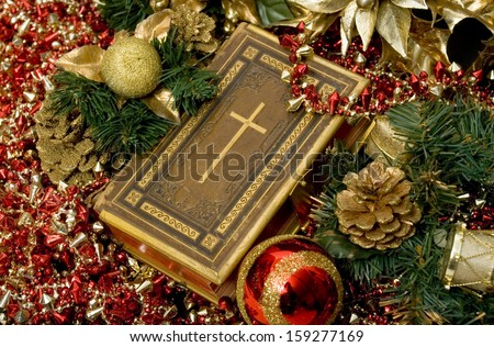 Selective focus on Bible surrounded by Christmas ornaments.