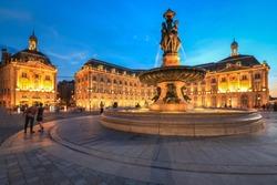Selective focus on building, People enjoy visiting Place de la Bourse at twilight, Place de la Bourse is one of the most recognizable sights of Bordeaux, France