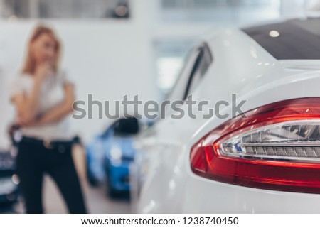 Selective focus on car lights of a modern automobile at the dealership, female customer looking at the auto on the background. Woman buying new car at dealership salon, copy space. Consumerism concept