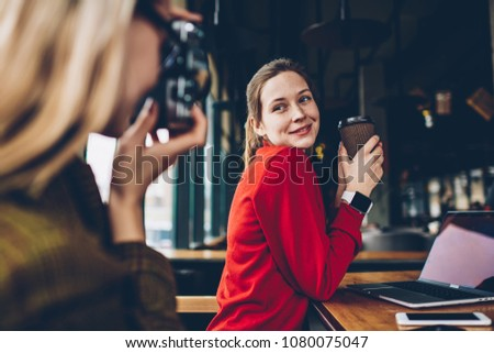 Selective focus on cheerful young woman with tasty caffeine beverage in hands posing and smiling while skilled female amateur focusing and making photos on vintage camera in leisure time in coworking #1080075047