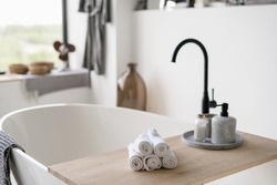 Selective focus on clean folded towels at wooden shelf on empty and contemporary tub with modern black water tap on blurred background. House decor at bright home with white interior design