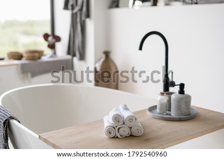 Selective focus on clean folded towels at wooden shelf on empty and contemporary tub with modern black water tap on blurred background. House decor at bright home with white interior design Stock photo ©