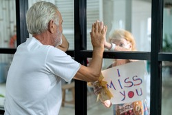 Selective focus on elderly covid-19 patients be isolated. Senior woman visiting husband in quarantine through window. Concepts of Home Isolation for Protecting vulnerable from Coronavirus infection.