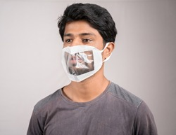 Selective focus on eyes, young man with transparent Medical face mask, to help hearing impairment or deaf people to understand lipreading during coronavirus or covid-19 outbreak