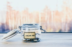 Selective focus on glass jar with text: swear jar, on it. Every time person curses or swears it has to put money as punishment in jar for safe keeps. Bad habit concept.