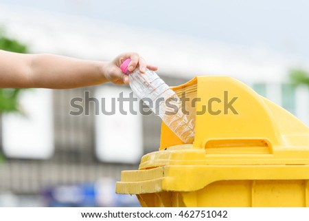 Selective focus on hand dropping empty plastic bottle to the yellow garbage bin. #462751042