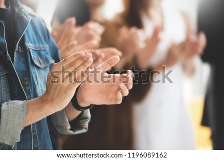 Selective Focus on hands. Creative designers audience applauding at a business seminar. Asian People listening and clapping at conference and presentation.
