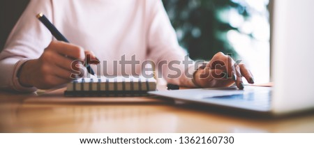 Selective focus on hipster girl writing interesting ideas for scenario for school performance while making research on content websites, woman typing text message via laptop keyboard for send reply Foto d'archivio ©