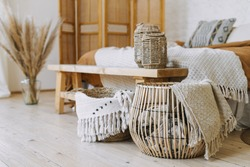 Selective focus on home decor. Comfortable bedroom in bohemian interior style with textile sheet on bed, wooden bench seat, bamboo dressing screen, dry plants in vase, wicker basket