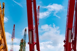 Selective focus on hydraulic of boom lift and crawler crane. Red crawler cranes use for reel lift-up equipment in construction site. Crane for rent. Crane dealership for a construction business.