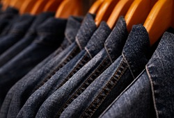 Selective focus on jacket jeans hanging on rack in clothes shop. Denim jeans with jeans pattern. Textile industry. Jeans fashion and shopping concept. Clothing concept. Denim jacket on rack for sale.