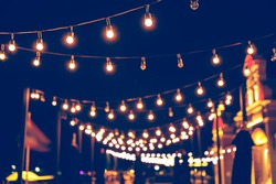 Selective focus on Light bulbs and  bokeh background with effect filter, Abstract background, vintage tone at night light festival.