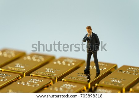 selective focus on miniature figure businessman standing on shiny gold bullions as financial investment and wealth concept.