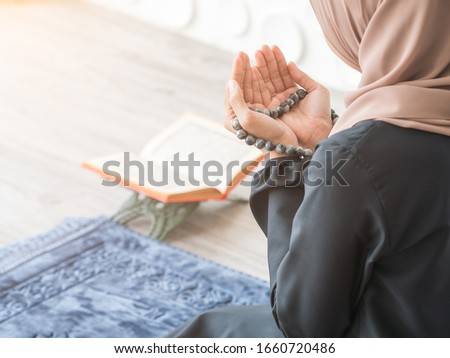 Selective focus on Moslem pray, praying hands to Allah with misbaha beads of Muslim lady with blurry quran resting on table stand beside blue mat.