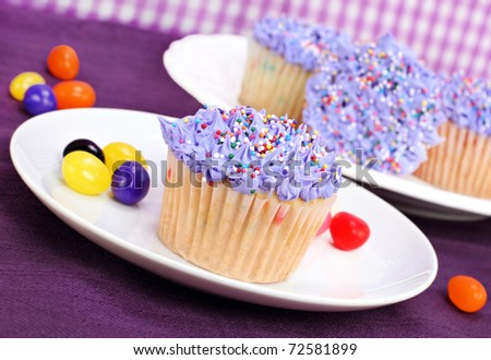 Selective focus on one pretty purple cupcake with jelly beans scattered.