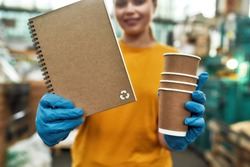 Selective focus on paper notebook produced from recycled cups held by girl working on waste station, cropped. Garbage sorting and recycling concept
