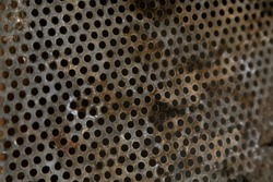 Selective focus on perforated metal sheet. Rusty metal texture with perforated holes metal corroded texture, rusty metal background perspective, texture for interior and exterior design
