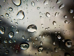 Selective focus on raindrops. Rain drops on window glass surface with blurry background. Natural pattern of raindrops isolated on blurry background.