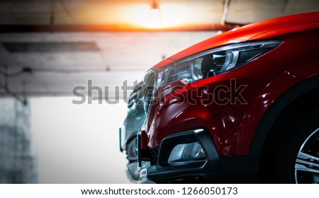 Selective focus on red shiny SUV sport car parked at shopping mall indoor parking lot. Headlamp lights with elegant and luxury design. Automotive industry and hybrid car concept. Underground parking. #1266050173