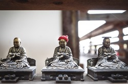 Selective focus on small bronze buddhist statues with coin and hat offerings, which are believed to make worshippers dreams come true in Daisho-in temple in Miyajima, Hiroshima, Japan