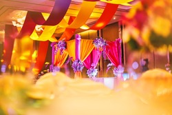 Selective focus on the colorful stage decoration with bright shade of color for bride and groom in the sangeet night of traditional indian wedding party celebration with blurry foreground