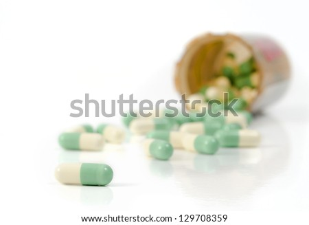 Selective focus on the foreground capsules spilled out of the pill bottle onto the white background