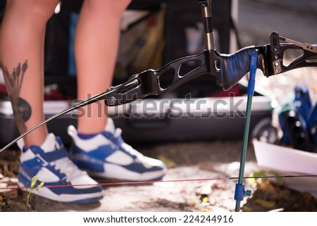 Selective focus on the great bow lying on the ground near the legs wearing nice sneakers on background