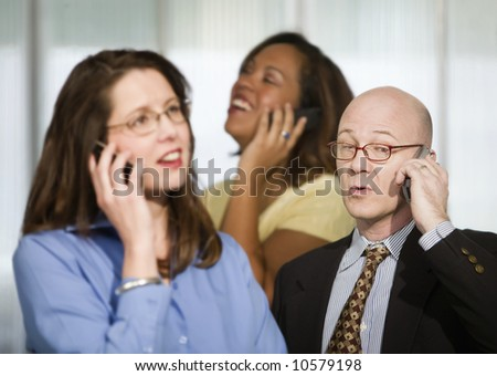 Selective focus on three businesspeople using cell phones