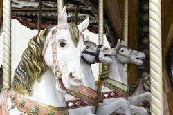 Selective focus on three white carousel horses