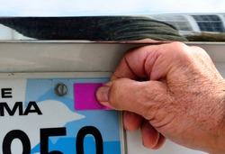 Selective focus on thumb pressing the blank annual license registration on rear license plate with copy or text space. The Man's righthand is pressing the blank violet sticker on the license plate.
