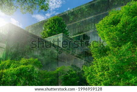 Selective focus on tree and eco friendly building with vertical garden in modern city. Green tree forest on sustainable glass building. Office building with green environment. Go green concept.