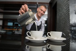 Selective focus on two white cups of coffee and metal jar with milk. Handsome young smiling barista wearing white shirt and black apron pouring the milk on background