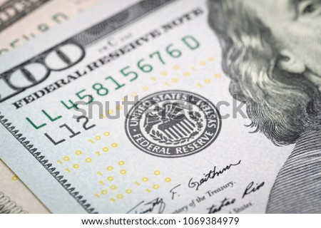 Selective focus on US Federal Reserve emblem on hundred dollars banknote as FED consider interest rate hike, economics and inflation control national organization.