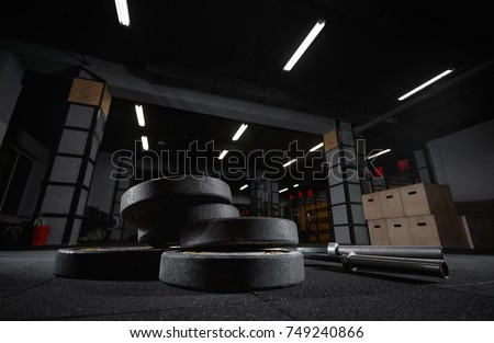 Selective focus on weights and gym equipment on the floor at fitness box weightlifting crossfit box training exercising space interior dark brutal motivation determination concept