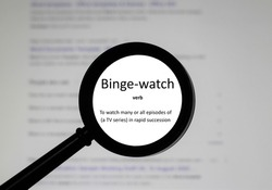 Selective focus on word Binge watch, word in a dictionary. Close up of an English dictionary page with word binge watch.